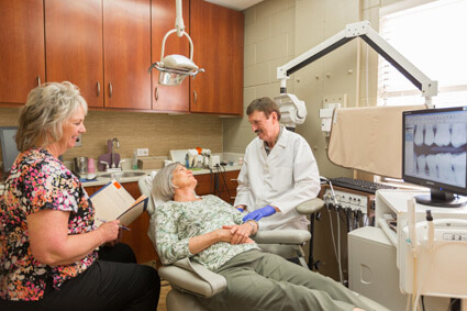 Dr. Malone and a dental assistant talk with a relaxing patient in Escondido, CA
